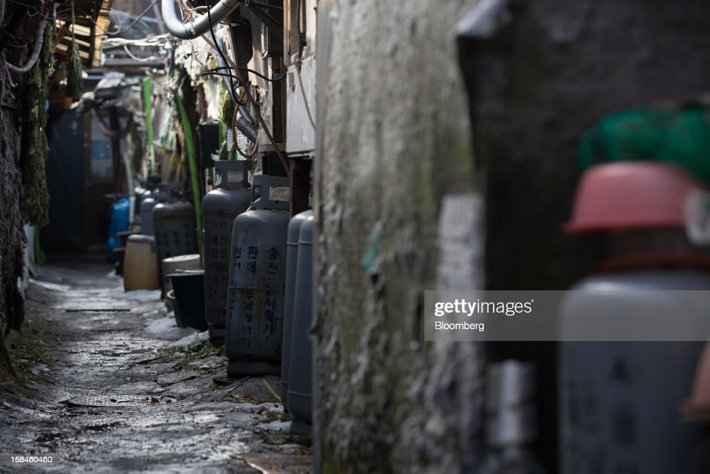 Butane gas tanks stand in an alley in Guryong village in the Gangnam district of Seoul, South Korea, on Sunday, Dec. 16, 2012. South Koreans vote on Dec. 19 to replace President Lee Myung Bak, whose five-year term ends in February. Photographer: SeongJoon Cho/Bloomberg via Getty Images