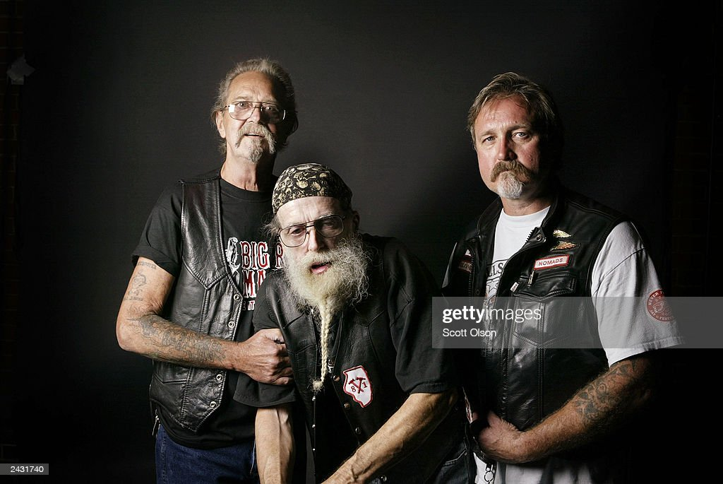 Butch (L) and Bud (C), members of the Midwest Percenters motorcycle club, stand with Jammer, a member of the Hells Angels motorcycle club as they attend a party hosted by the Midwest Percenters motorcycle club August 23, 2003 in Quincy, Illinois. Butch and Bud were bikers in Quincy when Jammer was growing up in the town. They inspired him to enter the lifestyle.