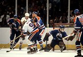 Butch Goring of the New York Islanders is checked by Randy Gregg of the Edmonton Oilers during the 1983 Stanley Cup Finals in May 1983 at the Nassau...