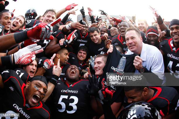 Butch Jones coach of the Cincinnati Bearcats celebrates with his team after the Bearcats defeated the Connecticut Huskies 3527 to claim their share...