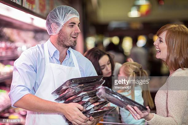 Butcher and client with packaged meat