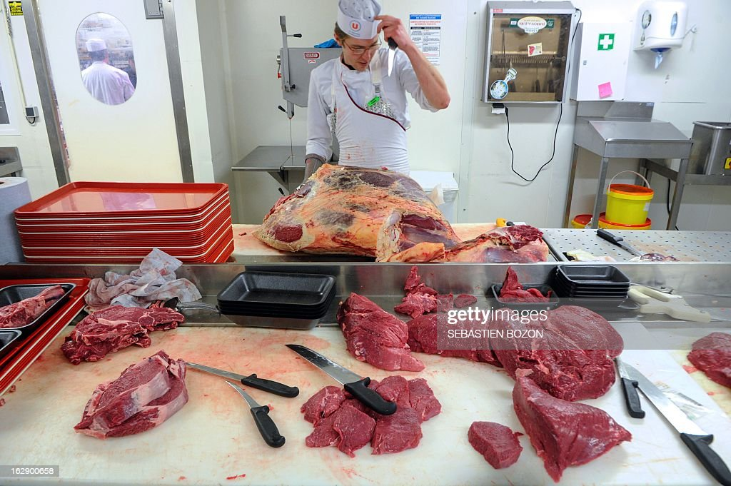 A butcher carves beef meat in a supermarket in Besançon, eastern France, on March 1, 2013. AFP PHOTO / SEBASTIEN BOZON