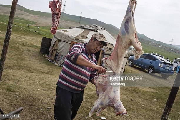 A butcher cuts a sheep's carcass at a livestock market on the outskirts of Ulaanbaatar Mongolia on Wednesday July 13 2016 The nation's growth slowed...