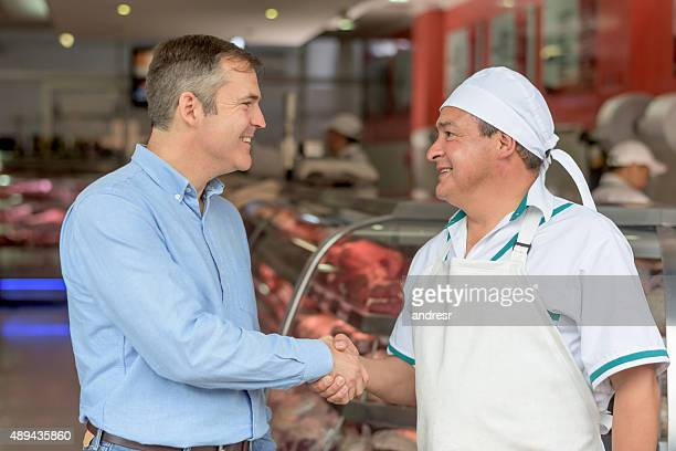 Butcher handshaking with a supplier