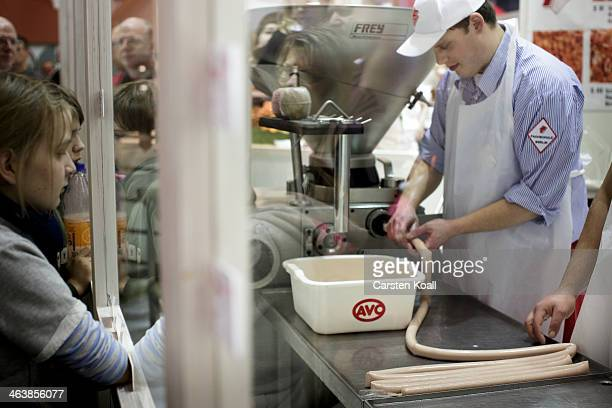 Butcher Hendrik Humpohl fills an intestine with a filling curry sausage at the Gruene Woche International Agriculture Fair on January 19 2014 in...