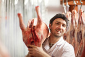 Butcher holding carcass over shoulder