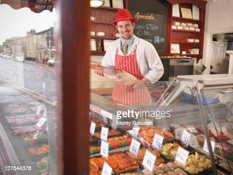 Butcher holding leg of lamb in shop