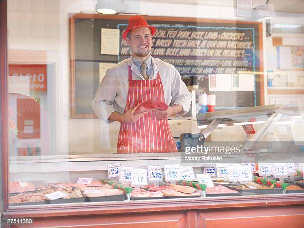Butcher holding steak behind counter