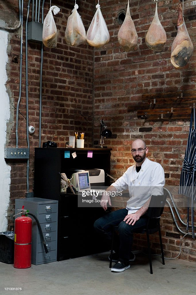 Butcher in office with hams : Stock Photo