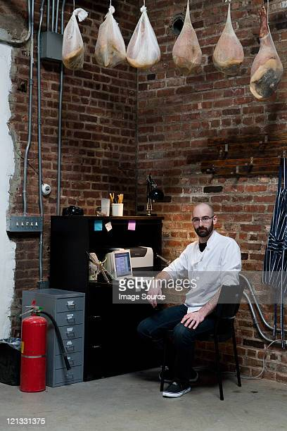 Butcher in office with hams
