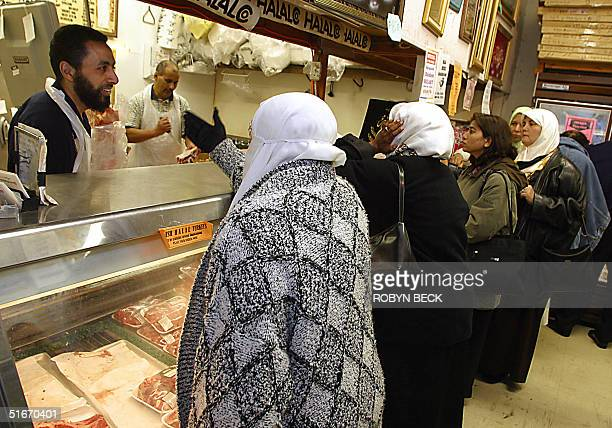 Butcher Khaled Megahed deals with a long line of customers waiting to buy meat for the Ramadan festival 05 November 2002 at a halal food shop in...