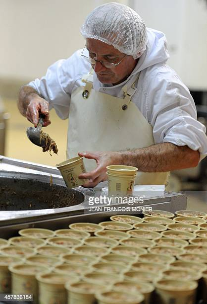 A butcher ladles 'rillettes' a meat preparation similar to pate into containers at the Charcuterie Cosme in Le Mans western France on October 25 2014...