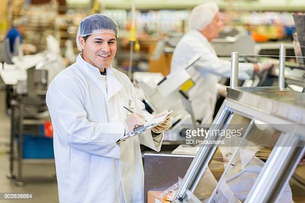 Butcher or deli manager in supermarket taking inventory