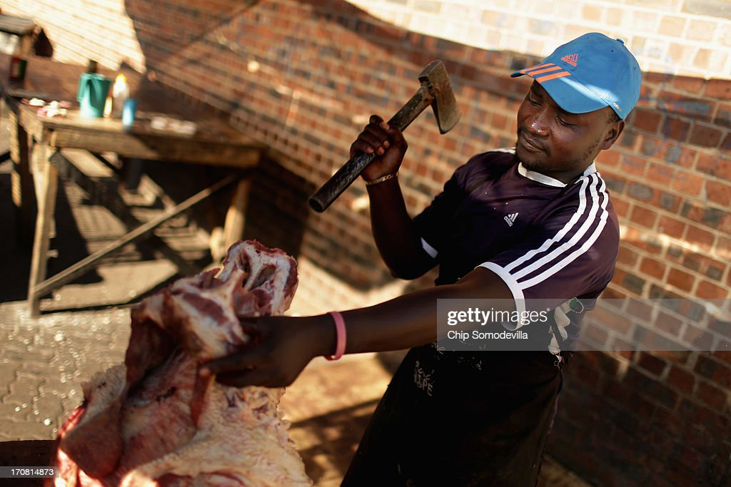 A butcher prepares a whole cow skull at the Farady Market near downtown June 18, 2013 in Johannesburg, South Africa. Farady is one of the oldest markets in Johannesburg for 'muti,' or herbs, animal parts, good luck charms and healing potions used as medicines for traditional healing.