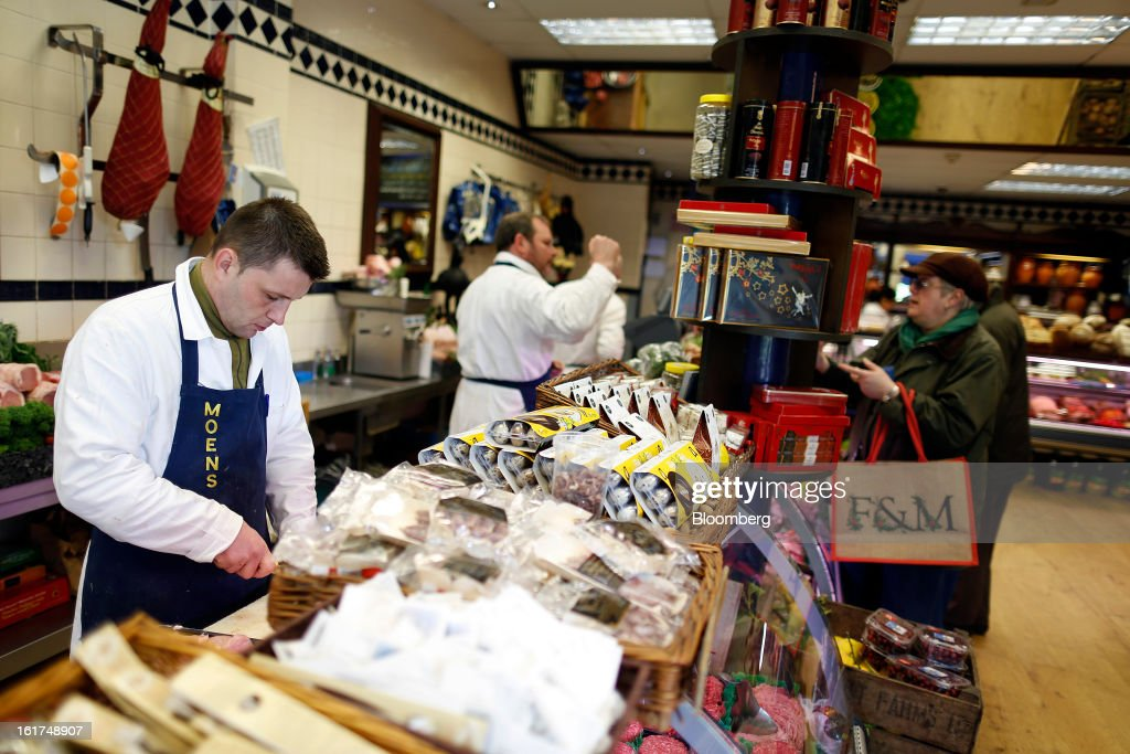 A butcher prepares meat on the counter as customers are served inside M.Moen & Sons butcher's shop in the Clapham district of London, U.K., on Friday, Feb. 15, 2013. While there's no evidence yet that consumer beef demand has slowed in the U.K., customers probably will spend more on higher quality cuts at meat counters or buy from independent butchers, Nick Allen, the executive director of the Agriculture & Horticulture Development Board's beef and lamb unit, known as Eblex, said. Photographer: Simon Dawson/Bloomberg via Getty Images