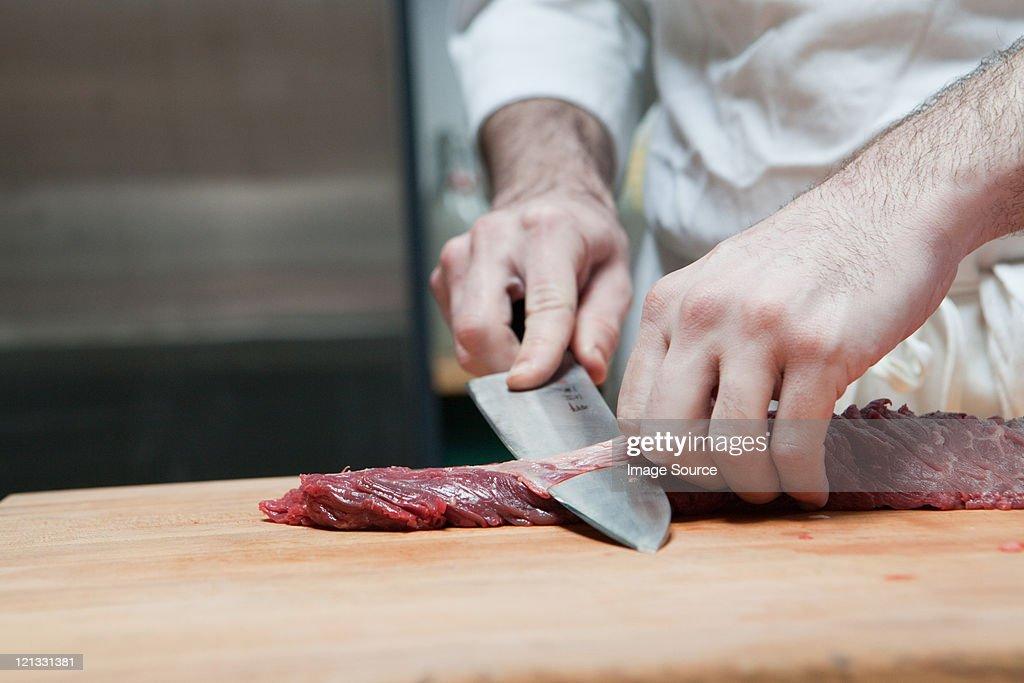 Butcher preparing beef tenderloin