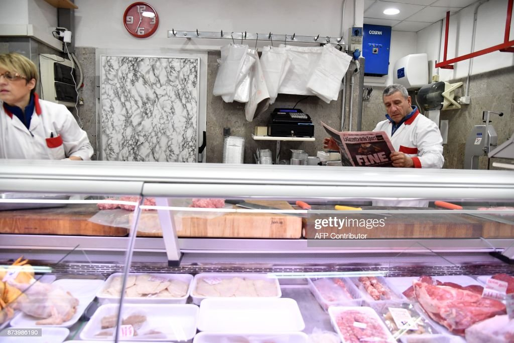 A butcher reads Italian sport newspaper 'Gazetta dello Sport' with a front page reading 'End' a day after the elimination of Italy during the FIFA World Cup 2018 qualification football match against Sweden, on November 14, 2017 in a food market in Rome. Italy failed to reach the World Cup for the first time since 1958 on Monday as they were held to a 0-0 draw in the second leg of their play-off at the San Siro by Sweden, who qualified with a 1-0 aggregate victory. / AFP PHOTO / Tiziana FABI