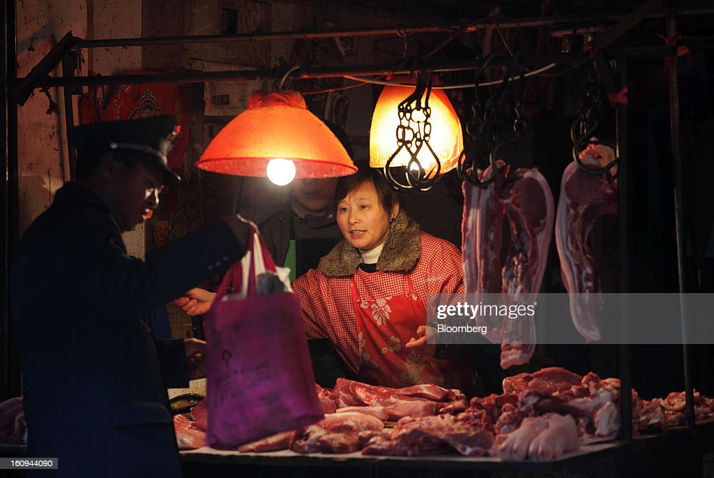 A butcher sells pork at a market in Shanghai, China, on Thursday, Feb. 7, 2013. China's consumer prices rose 2 percent in January from a year earlier while the producer-price index dropped 1.6 percent, the National Bureau of Statistics said today in Beijing. Photographer: Tomohiro Ohsumi/Bloomberg via Getty Images