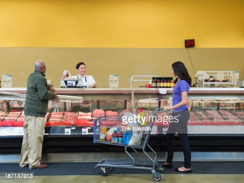 Butcher serving customers at meat counter of grocery store