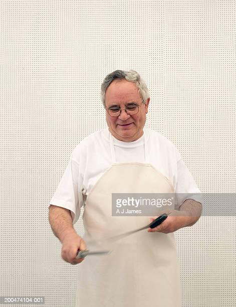 Butcher sharpening knives, smiling