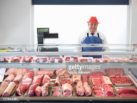 Butcher standing behind meat counter