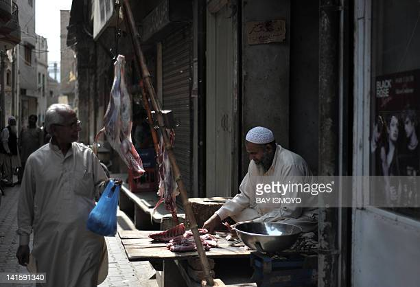 A butcher tends to his stall at a bazaar in the old town section of Multan on March 17 2012 Multan one of the oldest cities in the Asian subcontinent...