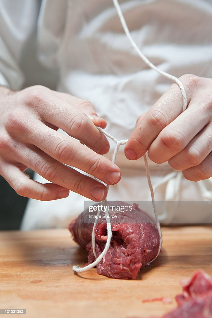 Butcher tying beef tenderloin with string : Stock Photo