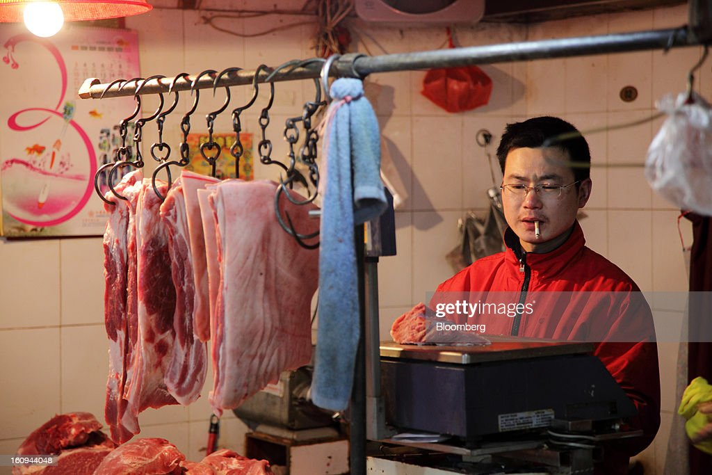 A butcher weighs a cut of pork at a market in Shanghai, China, on Thursday, Feb. 7, 2013. China's consumer prices rose 2 percent in January from a year earlier while the producer-price index dropped 1.6 percent, the National Bureau of Statistics said today in Beijing. Photographer: Tomohiro Ohsumi/Bloomberg via Getty Images