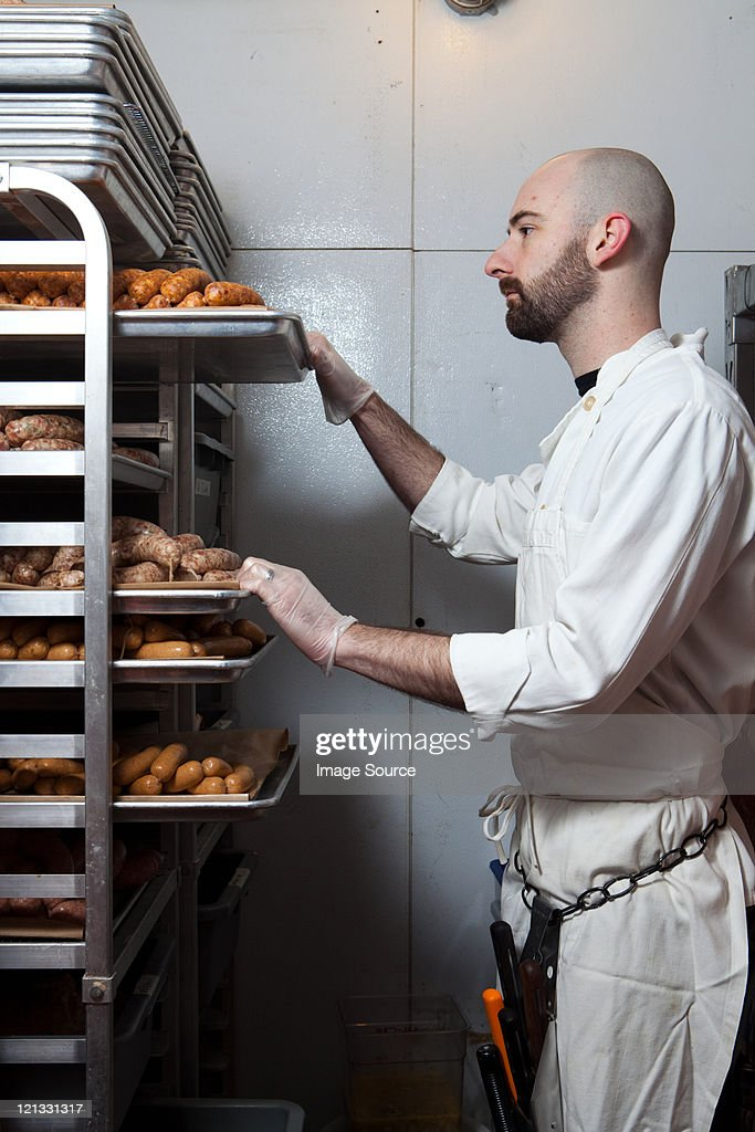 Butcher with racks of sausages on trays : Stock Photo