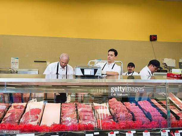 Butchers at meat counter of grocery store