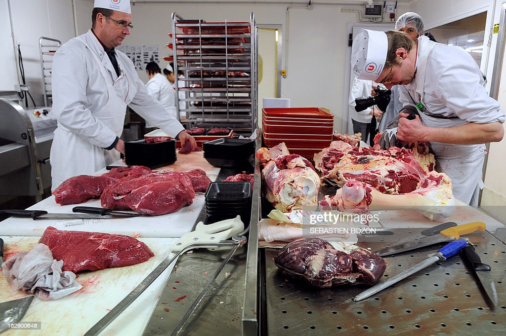 Butchers carve beef meat in a supermarket in Besançon, eastern France, on March 1, 2013.