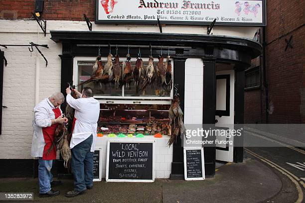 Butchers hector Guilbert and Alan Jones arrange game birds outside Andrew Francis butchers in the rural town of Ludlow in Shropshire on December 8...
