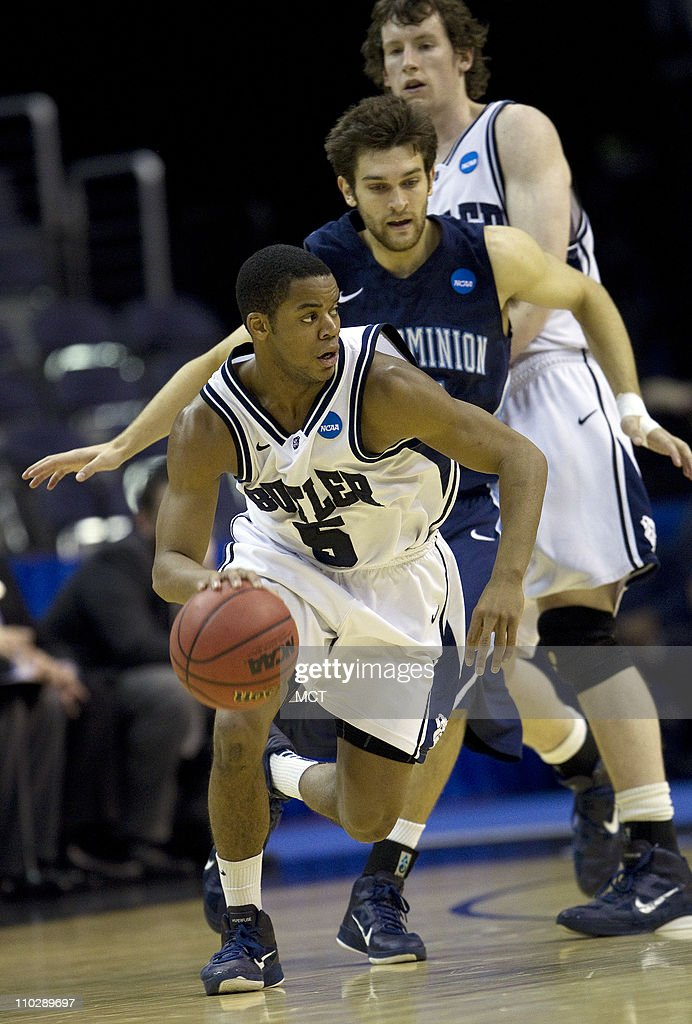 Butler guard Ronald Nored dribbles away from a screen set by teammate Andrew Smith back and Old Dominion defender Trian IIliadis center during...