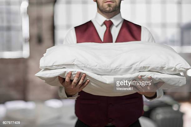 Butler in hotel room, holding pillows