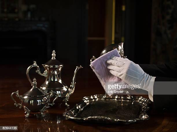 Butler polishing silver serving set.