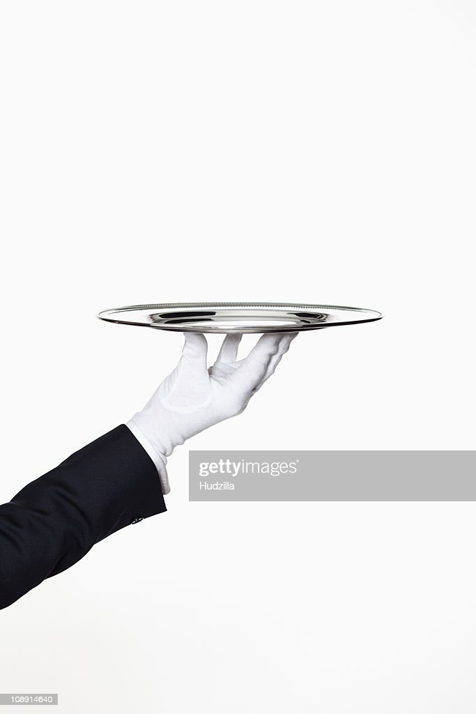 A butler presenting an empty silver tray, focus on hand