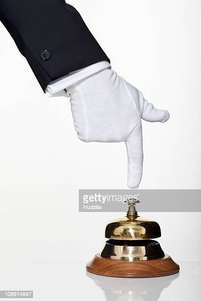 A butler pushing a service bell, focus on hand