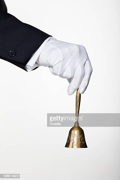 A butler ringing a hand bell for service, focus on hand
