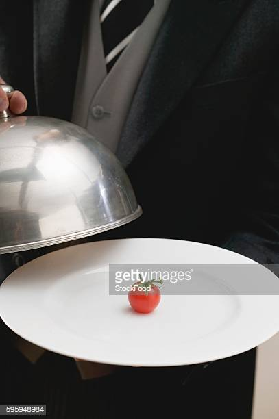 Butler serving cherry tomato on plate with dome cover