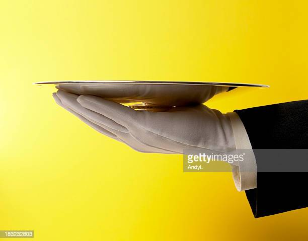 Butler Serving Empty Silver Tray on Yellow