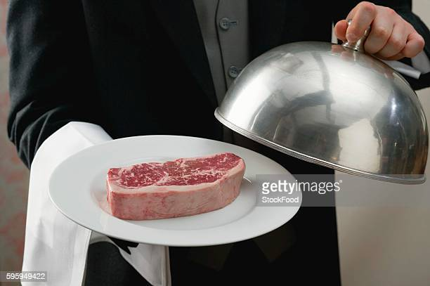 Butler serving raw beef steak on plate with dome cover