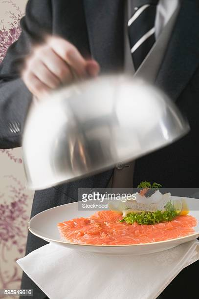 Butler serving smoked salmon with toast