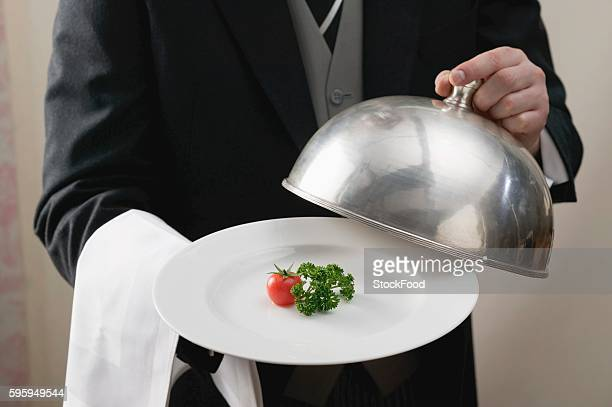 Butler serving tomato and parsley on plate with dome cover