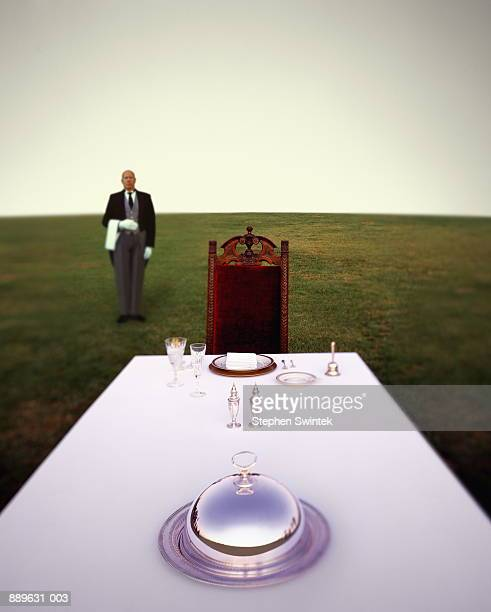 Butler standing behind table with setting (Digital Composite)