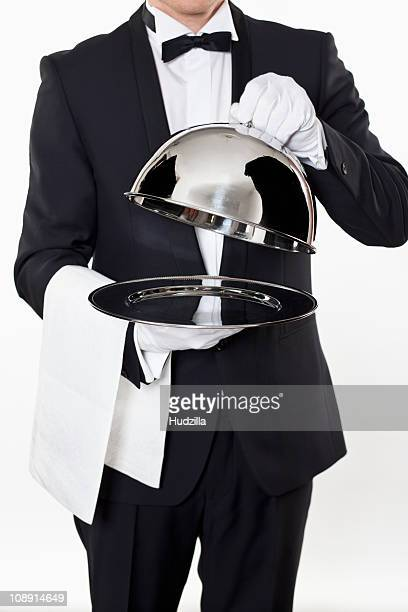 A butler taking the domed lid off an empty silver tray