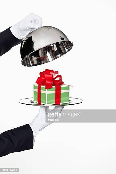 A butler taking the lid off a domed tray, revealing a gift, focus on hands