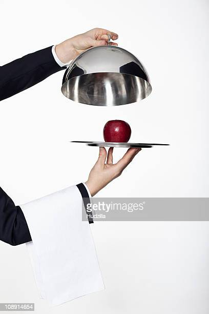 A butler taking the lid off a domed tray, revealing a red apple, focus on hands