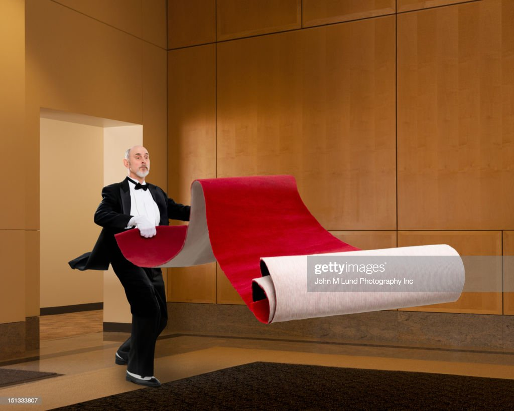 Butler unrolling red carpet : Stock Photo