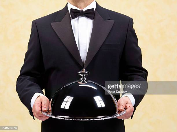 Butler, waiter holding domed silver tray, salver.