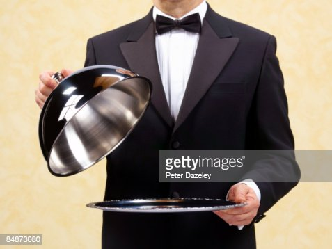 Butler waiter holding open domed silver tray.
